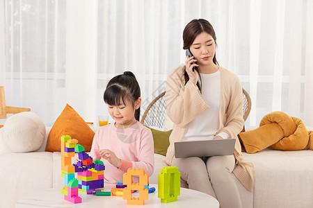 居家办公的年轻妈妈客厅陪伴女孩图片