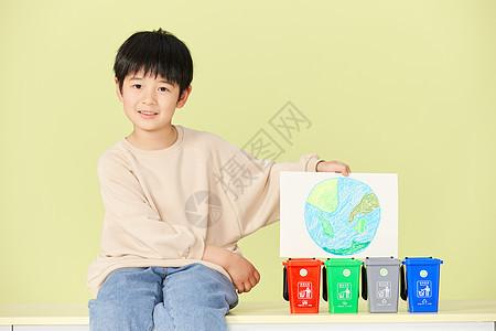小男孩坐在垃圾分类桶旁图片