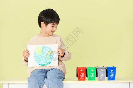 小男孩抱着手绘地球画看着垃圾分类桶图片