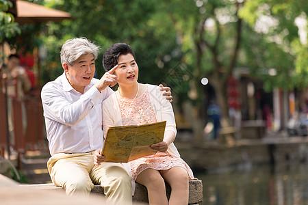 老年夫妻坐在河畔看地图图片