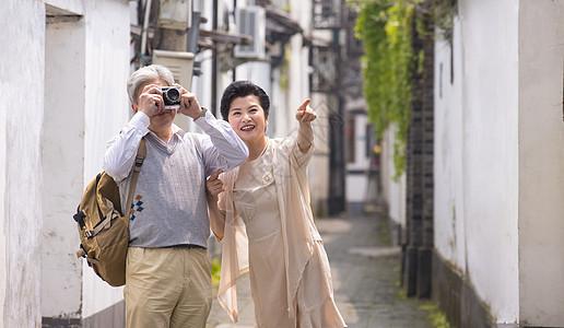 老年夫妻古镇巷子游玩拍照图片