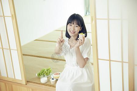 小清新美女居家吃蛋糕上的奶油图片