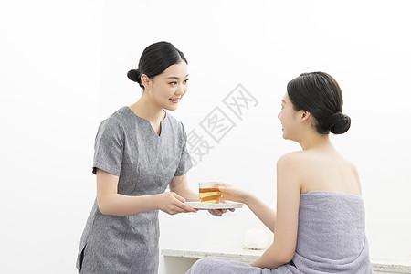 美容院按摩师为顾客服务端茶水图片