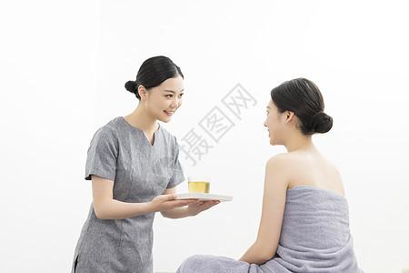 美容院按摩师为美女顾客服务递茶图片