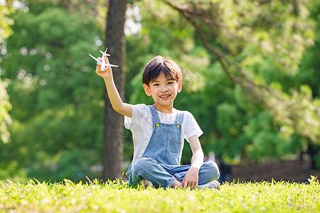 举起飞机模型的小男孩图片