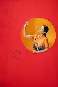 红色背景后的古典东方旗袍美女图片