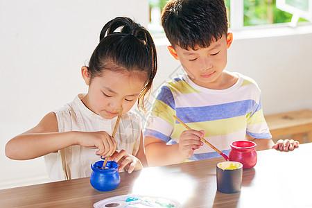 小朋友认真绘制陶艺品图片
