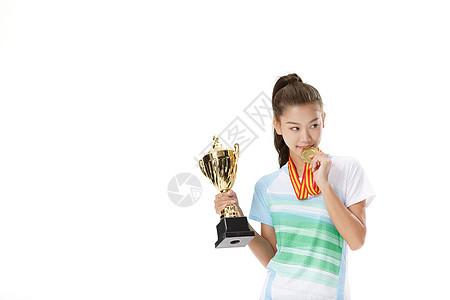 女性运动员手拿金牌和奖杯图片