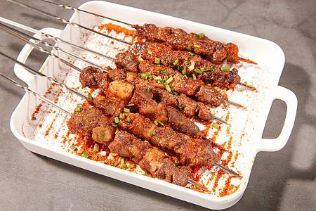 白色盘子里的羊肉串撒上辣椒粉和葱花图片