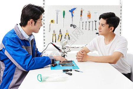 顾客和维修工人在维修店里交流图片