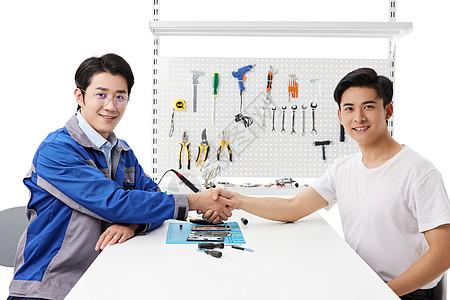 顾客和维修工人握手图片