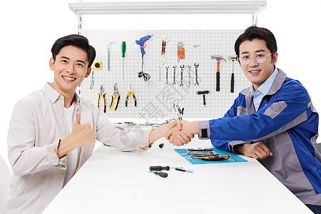 顾客和维修工人在维修店里握手点赞图片