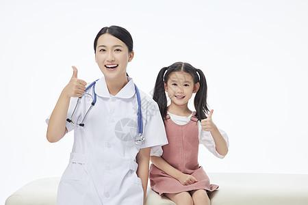 女护士和小朋友相伴坐病床上点赞图片