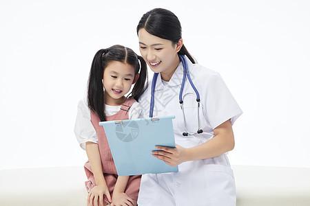 女医生和小女孩坐在病床上看病例图片