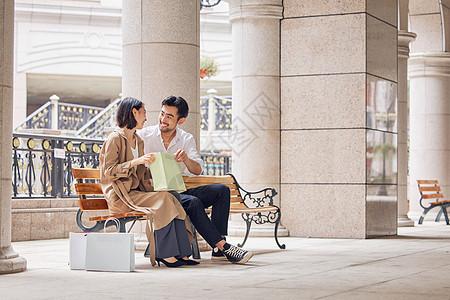 情侣坐在椅子上看购买到的商品图片