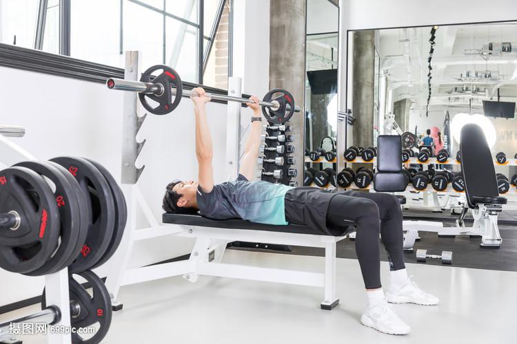 年轻男性健身房举哑铃力量训练